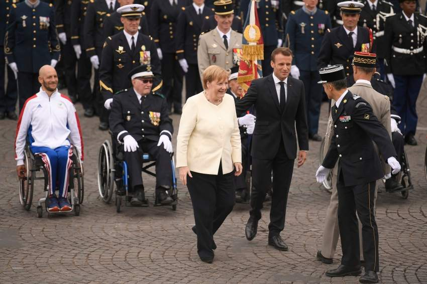 French President Emmanuel Macron (C,R) and German chancellor Angela Merkel (C) are seen among soldiers at the end of the Bastille Day military parade down the Champs-Elysees avenue in Paris on July 14, 2019. (Photo by Lionel BONAVENTURE / AFP)