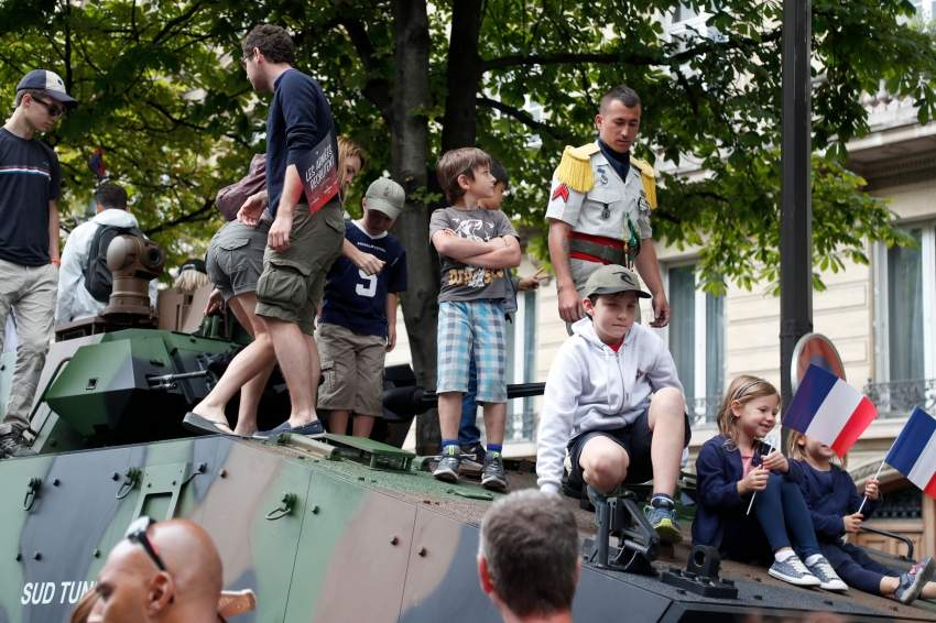 People stand on a tank on the sidelines of the annual Bastille Day military parade down the Champs-Elysees avenue in Paris on July 14, 2019. (Photo by Zakaria ABDELKAFI / AFP)