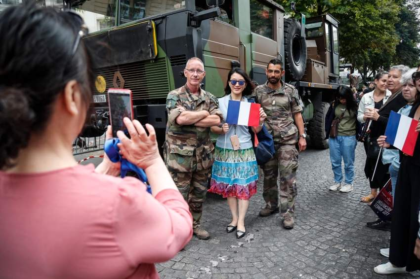 French soldiers pose with people on the sidelines of the annual Bastille Day military parade down the Champs-Elysees avenue in Paris on July 14, 2019. (Photo by Zakaria ABDELKAFI / AFP)