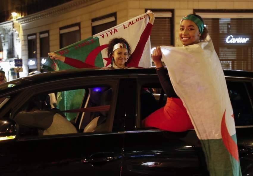 جزائريات يحملن العلم الجزائري ويحتفلن بالفوز - رويترز