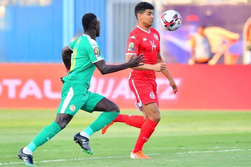 التونسي محمد دراجر في صراع على الكرة مع السنغالي سايدو ماني. (أ ف ب)