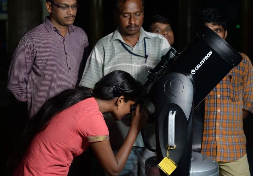 طفلة هندية تشاهد الخسوف الجزئي من خلال منظار خاص (أ.ف.ب)