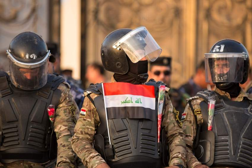 Members of the Iraqi security forces stand guard outside the Basra local government headquarters in the southern Iraqi city on July 19, 2019, with one of them having a miniature national flag attached to his body armour, as protesters gather for a demonstration against corruption, unemployment, and lack of public services. (Photo by Hussein FALEH / AFP)