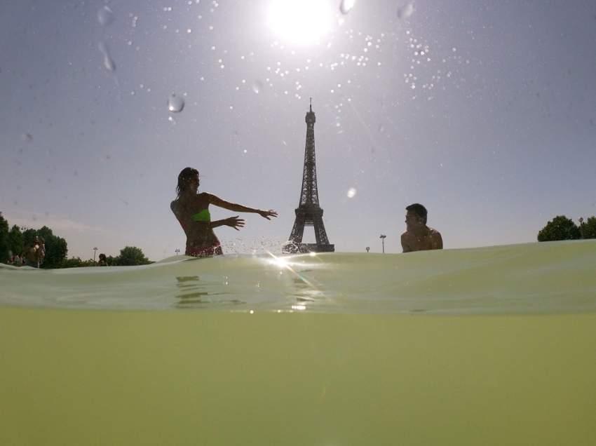نافورة تروكاديرو الشهيرة بالقرب من برج إيفل تشهد إقبالاً كبيرا من الباريسيين والسياح للتغلب على ارتفاع درجات الحرارة (أ.ف.ب)