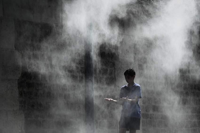 مرشات مياه منتشرة في شوارع باريس للتخفيف من ارتفاع درجات الحرارة (أ.ف.ب)