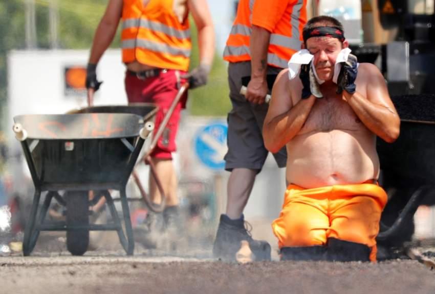 عامل ألماني يقوم بمسح وجهه في أحد الشوارع في العاصمة الألمانية برلين حيث سُجلت أعلى درجة حرارة 3 درجة مئوية (رويترز)