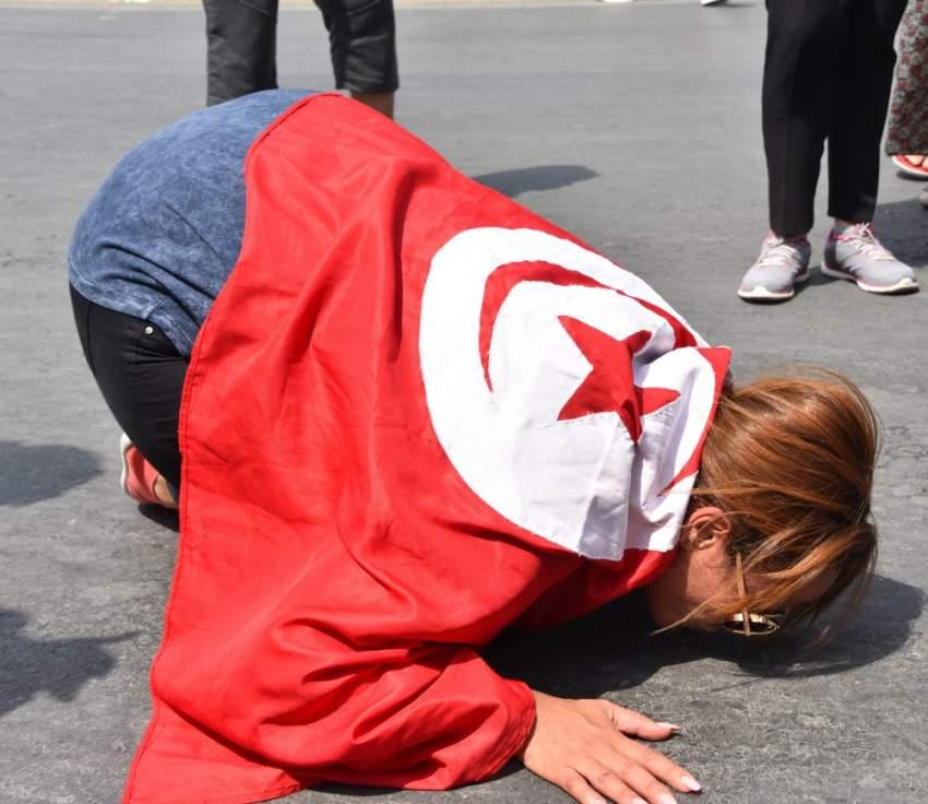 مواطنة تونسية ترتدي العلم التونسي وتنهار أرضاً خلال تشييع الرئيس الراحل الباجي قايد السبسي - رويترز
