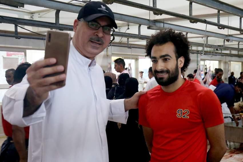 في الكويت أحدهم يصادف قصاب مصري أثناء التجهيز للأضحيات ويلتقط معه صورة نظراً للشبه الكبير بينه وبين نجم ليفربول محمد صلاح (أ ف ب)