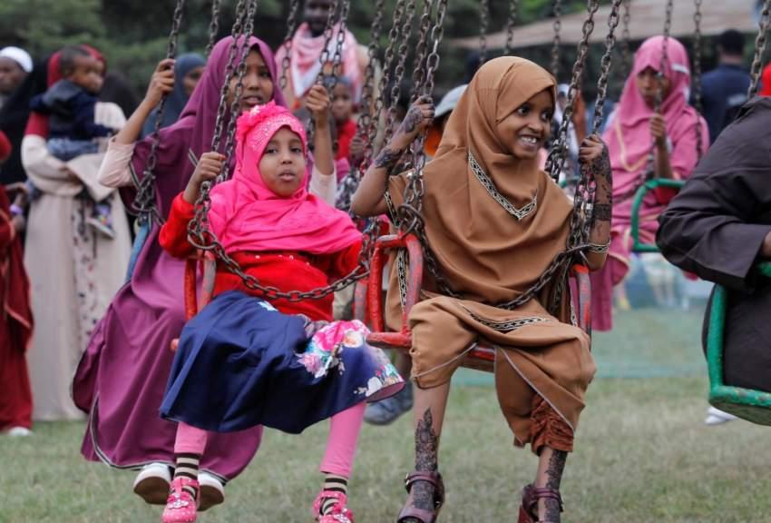 فتيات يلعبن على الأراجيح مبتهاجات بفرحة عيد الأضحى في كينيا (رويترز)