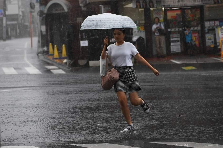 يابانية تحتمي بمظلة من مياه الأمطار في طوكيو.