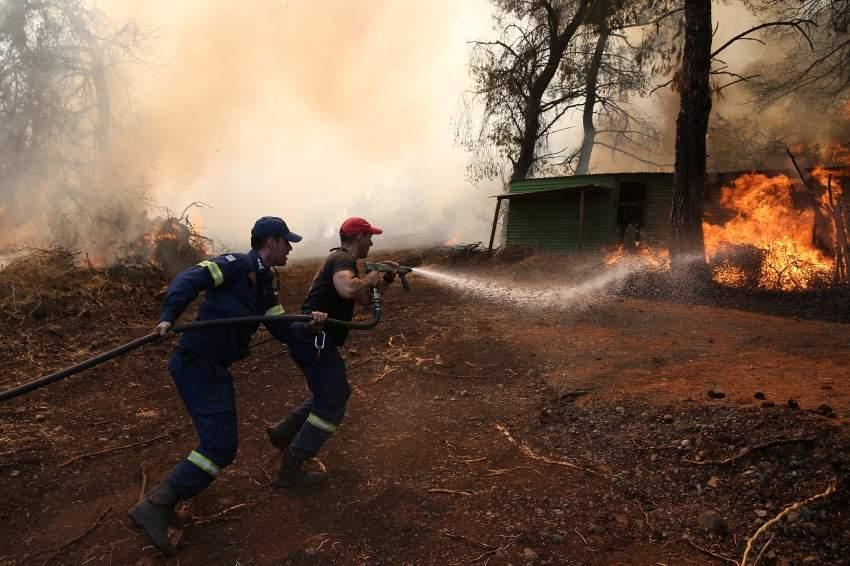رجال الإطفاء يحاولون السيطرة على حريق في جزيرة إيفيا اليونانية.