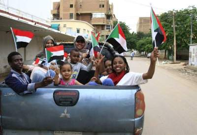 سودانيون يلوّحون بالأعلام احتفالاً بتوقيع الاتفاق التاريخي. (أ ف ب)
