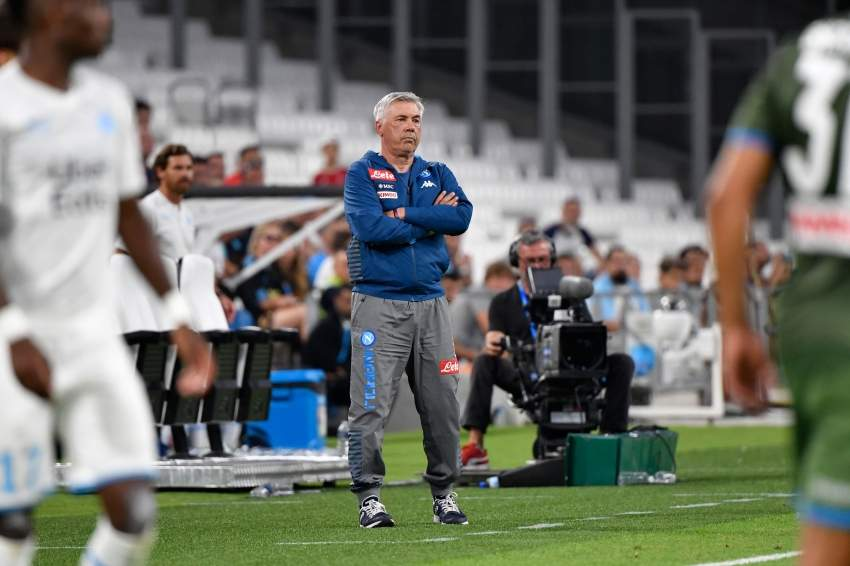 (FILES) In this file photo taken on August 4, 2019 Napoli's Italian coach Carlo Ancelotti (R) looks on before the international friendly football match between Olympique de Marseille (OM) and SSC Napoli at the Velodrome Stadium in Marseille, southern France. - As the sole survivor of a coaching shuffle among the leading challengers, Carlo Ancelotti could have the best chance to end Napoli's 30-year wait for the Serie A title. Yet Antonio Conte's arrival at Inter Milan has also raised expectations of an end to Juventus's long domination in the season that kicks off on August 24, 2019. (Photo by GERARD JULIEN / AFP)