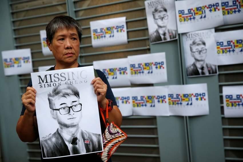 متظاهر يحمل صورة سايمون تشنغ. (رويترز)