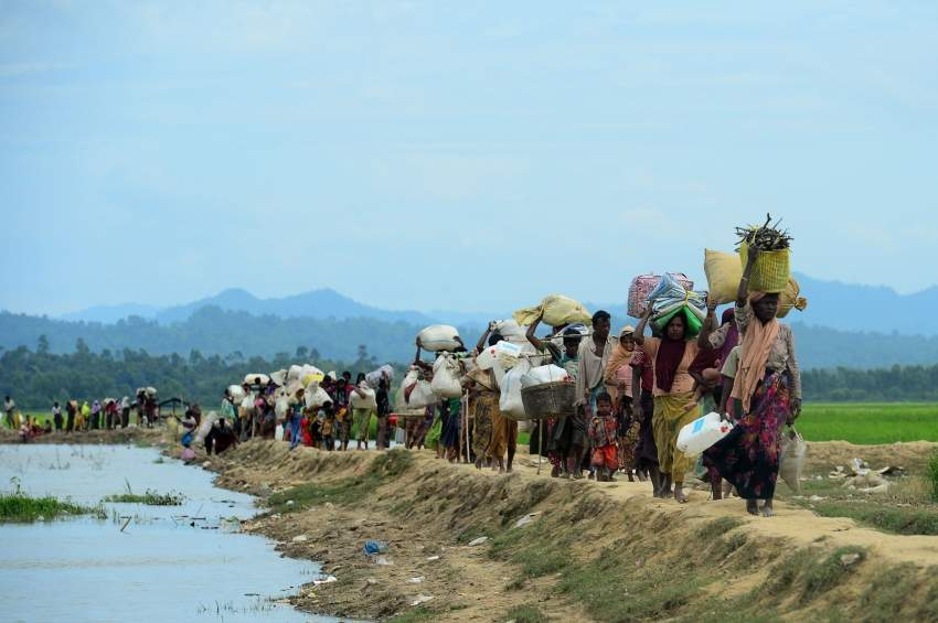 (FILES) In this file photo taken on October 19, 2017 Rohingya refugees who were stranded walk near the no man's land area between Bangladesh and Myanmar in the Palongkhali area next to Ukhia. - Some 200,000 Rohingya rallied in a Bangladesh refugee camp on August 25, 2019 to mark two years since they fled a violent crackdown by Myanmar forces, just days after a second failed attempt to repatriate the refugees. (Photo by Munir UZ ZAMAN / AFP)