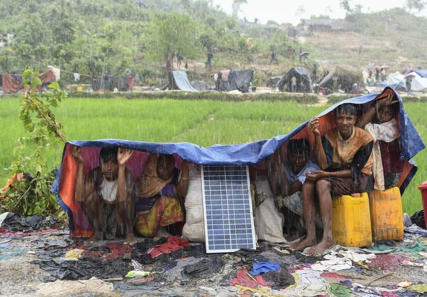 (FILES) In this file photo taken on September 17, 2017 Rohingya refugees protect themselves from the rain in Bangladesh's Balukhali refugee camp. - Some 200,000 Rohingya rallied in a Bangladesh refugee camp on August 25, 2019 to mark two years since they fled a violent crackdown by Myanmar forces, just days after a second failed attempt to repatriate the refugees. (Photo by DOMINIQUE FAGET / AFP)
