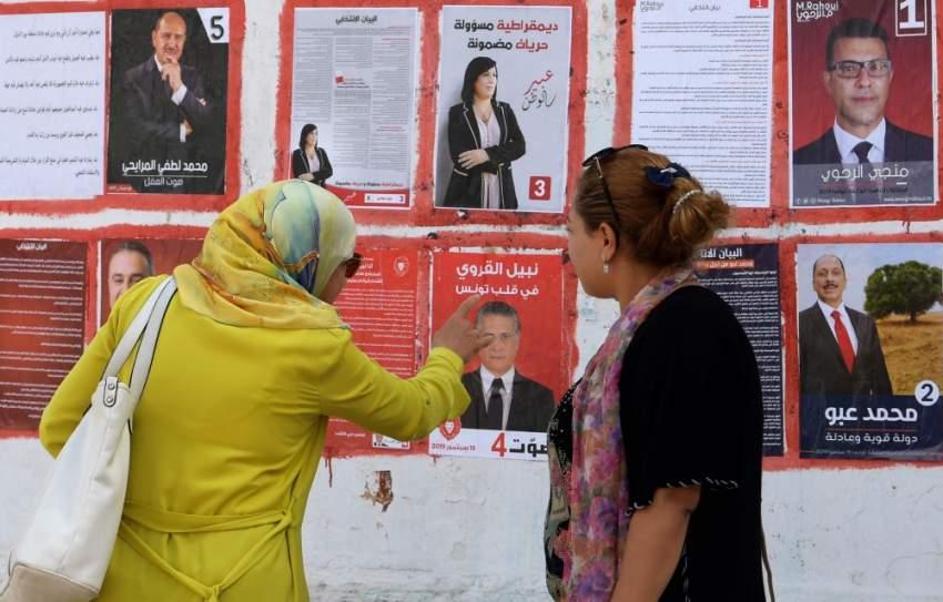تونسيات أمام ملصقات مرشحين للانتخابات الرئاسية. (أ ف ب)