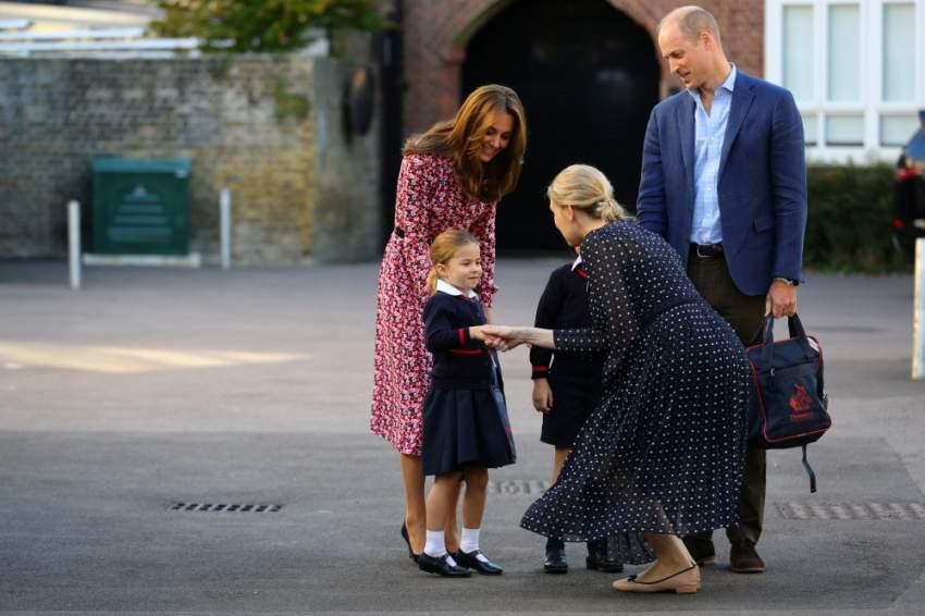 هيلين هاسلم مديرة المدرسة تحيي الأميرة البريطانية شارلوت لدى وصولها المدرسة في أول أيامها بصحبة والدتها دوقة كمبردج كيت ووالدها دوق كمبردج وليام وشقيقها الأمير جورج في لندن يوم الخميس. (رويترز)