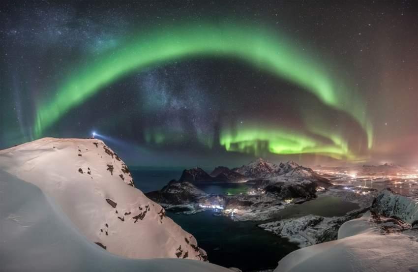 3. اضطر المصور للتسلق إلى قمة جبل في النرويج، غير آبه بالثلوج، ليتحفنا بمنظر الشفق القطبي العملاق المذهل فوق جزر لوفوتين. (نيكولاي بروغر)