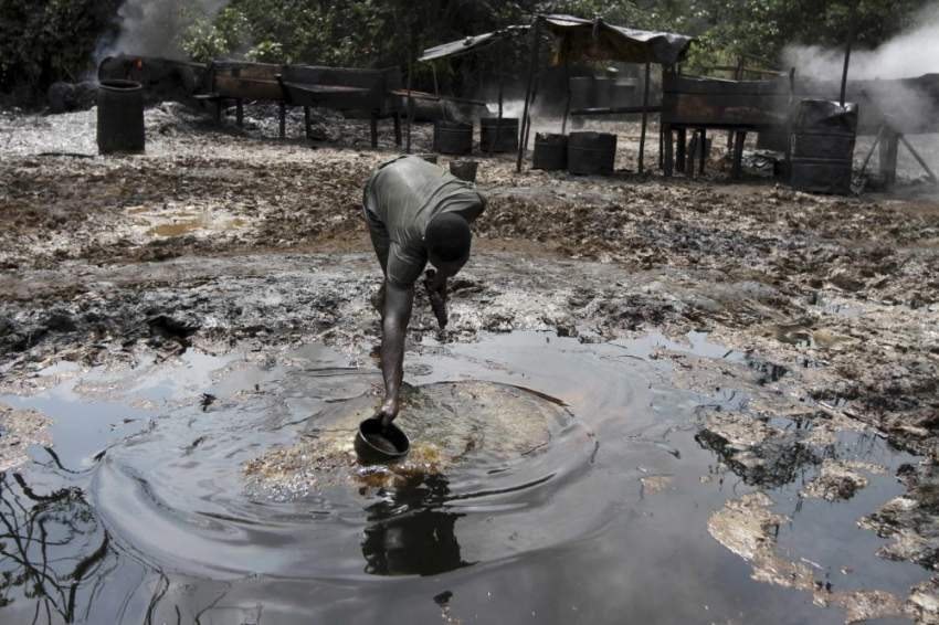 A man collects polluted water at an illegal oil refinery site near river Nun in Nigeria's oil state of Bayelsa November 27, 2012. Thousands of people in Nigeria engage in a practice known locally as 'oil bunkering' - hacking into pipelines to steal crude then refining it or selling it abroad. The practice, which leaves oil spewing from pipelines for miles around, managed to lift around a fifth of Nigeria's two million barrel a day production last year according to the finance ministry. Picture taken November 27, 2012. REUTERS/Akintunde Akinleye    (NIGERIA - Tags: BUSINESS ENVIRONMENT SOCIETY INDUSTRIAL ENERGY) ATTENTION EDITORS - PICTURE 16 OF 28 FOR PACKAGE 'NIGERIA'S ILLEGAL OIL BUNKERERS'. SEARCH 'OIL BUNKERING' FOR ALL IMAGES