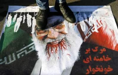 متظاهر يدهس صورة خامنئي خلال احتجاج أمام سفارة إيران في تبليسي (د ب ا)
