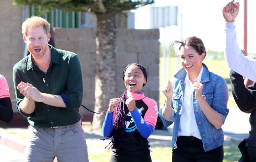 ميغان وهاري لا يستطيعان إخفاء ابتسامتهما بعد لقائهما عدداً من أعضاء منظمة «موجات من أجل التغيير»