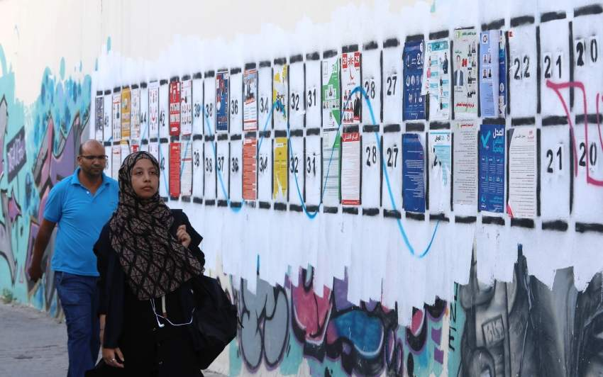تونسيون يمرون بجوار قوائم المرشحين في الانتخابات التشريعية (إي بي أيه)