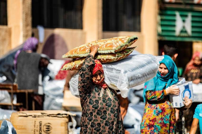 A displaced Syrian woman, who fled her home in the border town of Ras al-Ain, receives humanitarian aid on October 12, 2019, in the town of Tal Tamr in the countryside of Syria's northeastern Hasakeh province. - Ras al-Ain would be the first town to fall to Ankara's forces since the launch of its cross-border offensive earlier in the week. Both it and Tal Abyad further west have been major goals of the invasion as Turkey seeks to impose its control over the area between them which although Kurdish-controlled, is mainly ethnic Arab. (Photo by Delil SOULEIMAN / AFP)