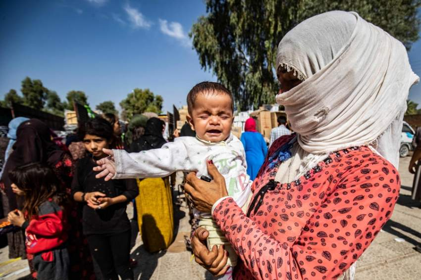Displaced Syrians, who fled their homes in the border town of Ras al-Ain, receive humanitarian aid on October 12, 2019, in the town of Tal Tamr in the countryside of Syria's northeastern Hasakeh province. - Ras al-Ain would be the first town to fall to Ankara's forces since the launch of its cross-border offensive earlier in the week. Both it and Tal Abyad further west have been major goals of the invasion as Turkey seeks to impose its control over the area between them which although Kurdish-controlled, is mainly ethnic Arab. (Photo by Delil SOULEIMAN / AFP)
