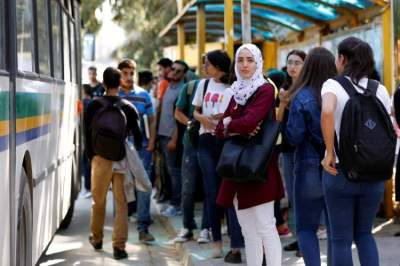 شباب تونسيون في محطة حافلات خارج جامعة المنار  (رويترز)