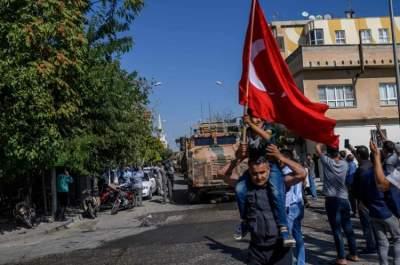 تركي يلّوح بعلم بلاده تأييداً للغزو التركي على شمال سوريا. (أ ف ب)