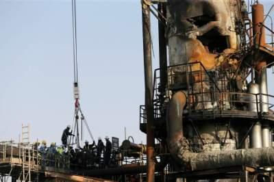 عمال عند موقع استهداف منشأة نفطية تابعة لأرامكو في السعودية. (رويترز)