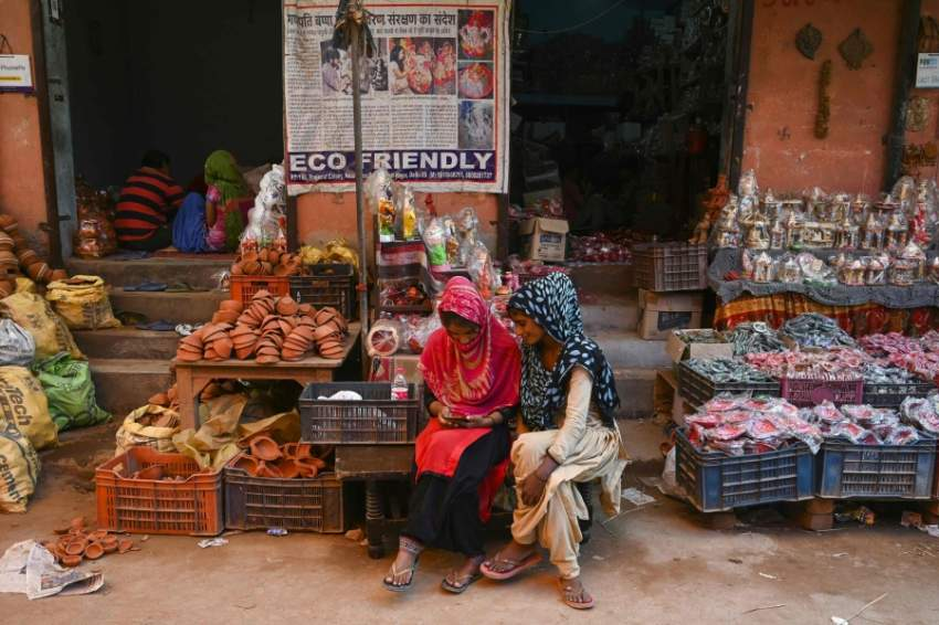 """In this photograph taken on October 4, 2019, women use a mobile phone as they sit outside their shop displaying items made of clay, at Kumhar Gram (Potter's Village) in New Delhi. - The narrow lanes of Kumhar Gram are buzzing with activity ahead of Diwali as generations of potters race to create clay decorations for customers across the country -- and beyond. Known as the """"Potter's Village"""", the settlement is home to around 500 families from India's traditional pottery community, who moved to the area half a century ago. (Photo by Money SHARMA / AFP)"""