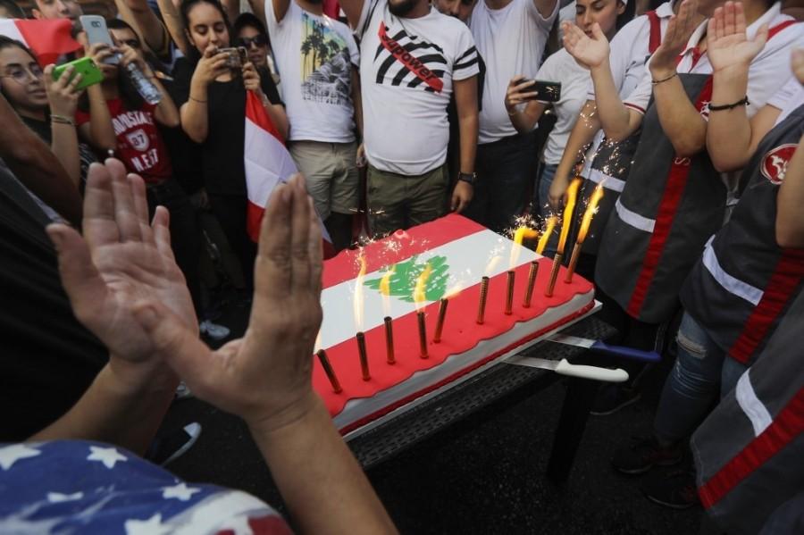 جموع من المتظاهرين اللبنانين يحضرون كيك مزين بالعلم اللبناني