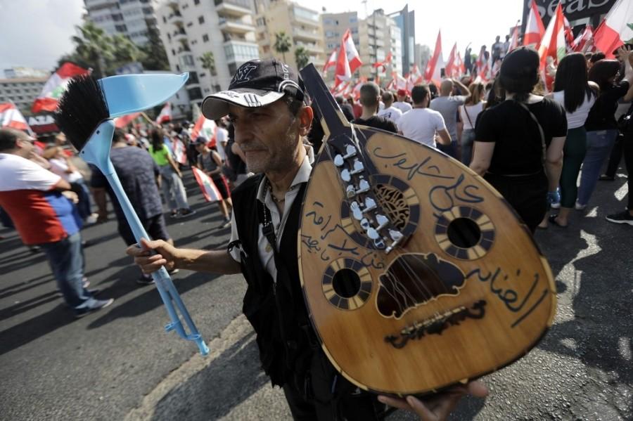 أحد المتظاهرين يوجه رسالة من آلة العود الخاصة به