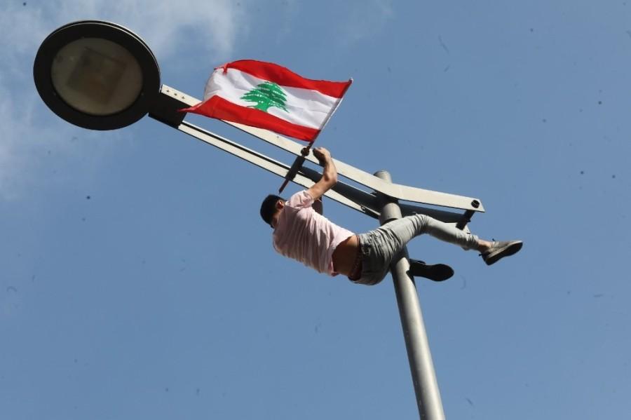 أحد المتظاهرين يرفع العلم على عمود الكهرباء