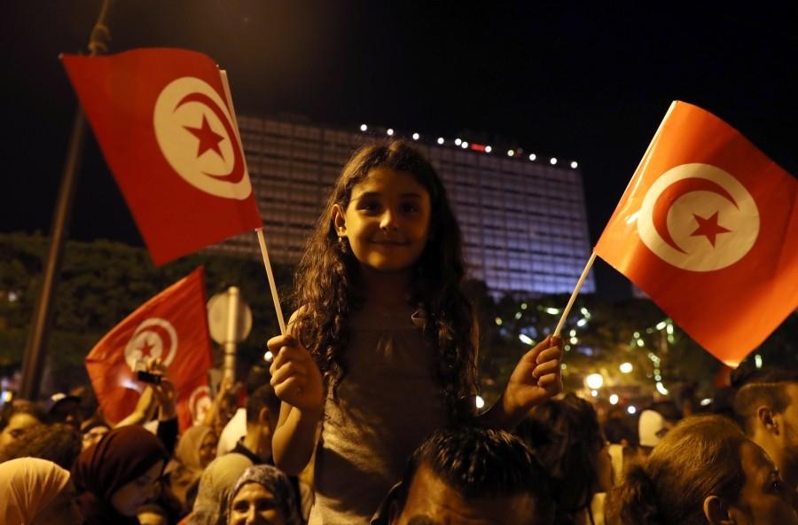 تونسيون يحتفلون بإعلان فوز قيس سعيد بانتخابات الرئاسة وسط العاصمة. (إي بي إيه)