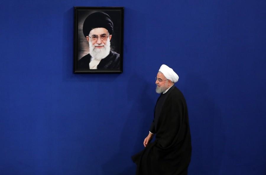 روحاني يسير بجوار صورة خامنئي قبل مؤتمر صحفي بطهران (