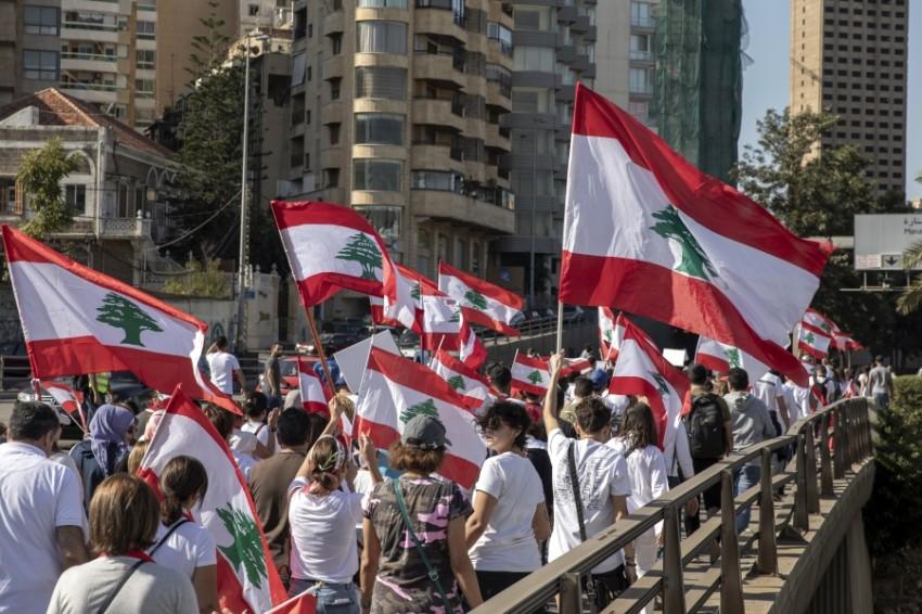 علم لبنان مرفرفاً في أيدي المحتجين في «أحد الشهداء». (إي بي أي)