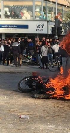 متظاهرون إيرانيون يتجمعون بالقرب من دراجة نارية مشتعلة. (أ ف ب)