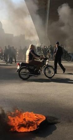 متظاهرون يقطعون طريقاً في إيران. (أ ف ب)
