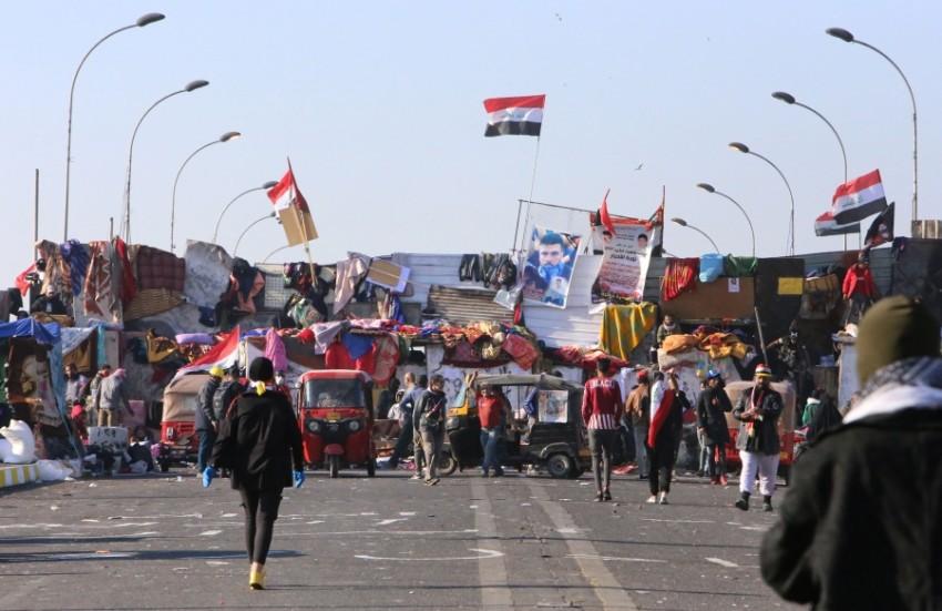 متظاهرون عراقيون يقطعون جسر السنك في بغداد. (أ ف ب)