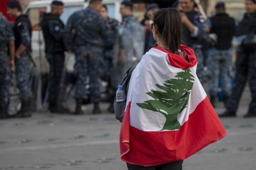 محتجة لبنانية تسير أمام قوات أمن في بيروت. (إي بي أيه)