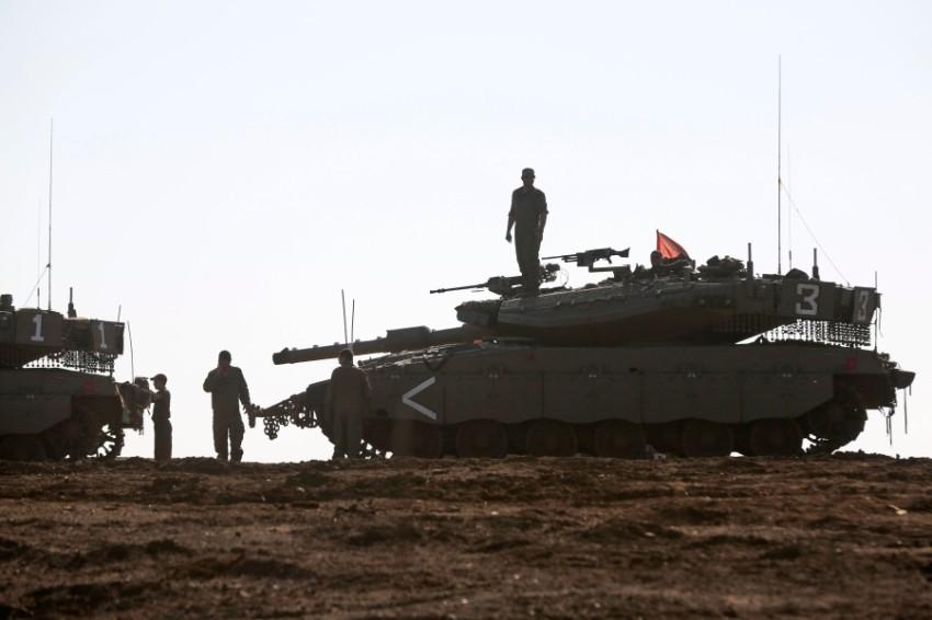 جنود إسرائيليون قرب دبابات خلال العمليات العسكرية في الجولان المحتلة. (أ ف ب)