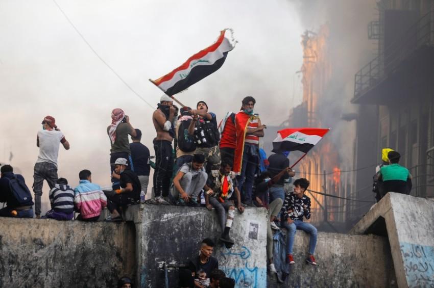 متظاهرون عراقيون يرفعون العلم خلال احتجاج ضد الحكومة في بغداد. (رويترز)