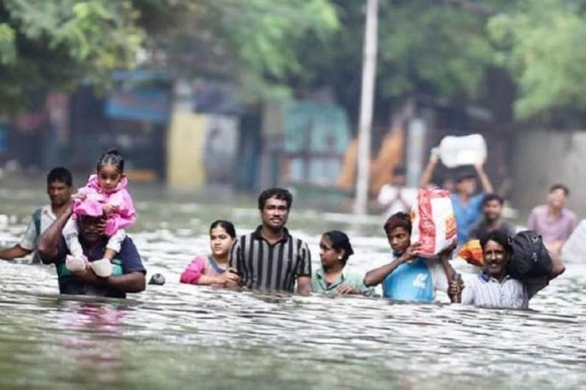 عائلة تخوض في مياه الأمطار الموسمية بالهند. (أرشيفية)