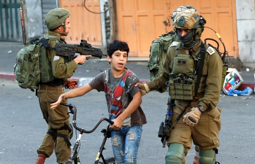 جنود الاحتلال يعتقلون طفلاً في الخليل بالضفة. (إي بي أيه)