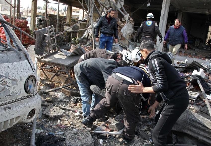 سوريون يجمعون أشلاء القتلى في معرة النعمان بإدلب. (أ ف ب)