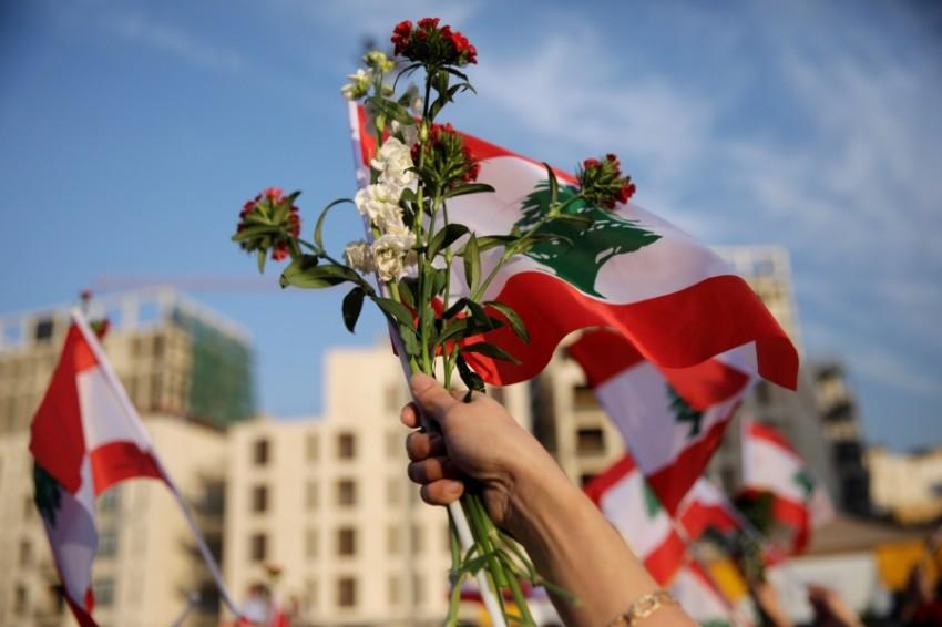 متظاهرة تحمل العلم اللبناني وورود خلال احتجاجات في بيروت. (رويترز)