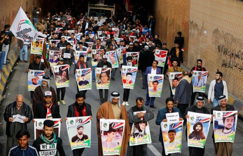 متظاهرون عراقيون يحملون صور قتلى الاحتجاجات في الناصرية. (رويترز)
